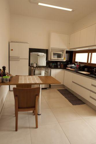 Cozinha com piso porcelanato (Porto Bello Bauhaus 60 x 60 cm) e armários, da Cidlar Móveis Planejados, em mdf branco texturizado. A mesa parafusada na parede tem pé de alumínio e é feita de madeira revestida com fórmica, também da Cidlar Móveis Planejados