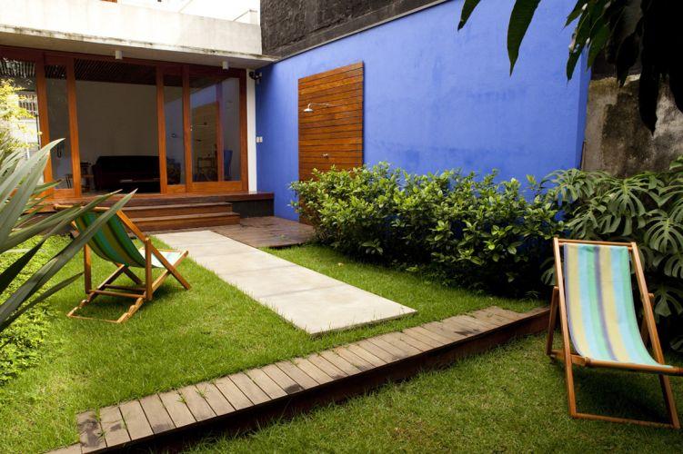 Muro pintado de tinta acrílica fosca azul com painel e deck de madeira Cumaru. O encanamento do chuveiro da Deca foi embutido na alvenaria. O ambiente foi anexado ao sobrado reformado por Ana Sawaia, em São Paulo