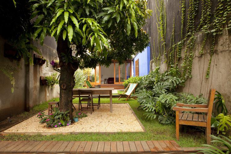 Jardim nos fundos da casa com projeto de reforma da arquiteta Ana Sawaia. Foram usadas grama esmeralda e amendoim, além de gardênias e fórmios. Junto ao anexo foi definido um espaço para refeições ao ar livre, sobre uma caixa revestida com pedriscos, à sombra da mangueira