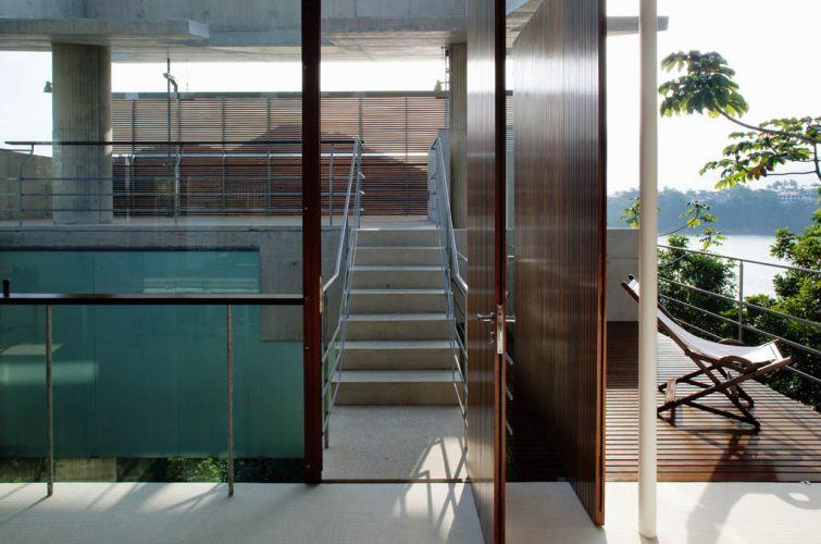 Escada une a sala de estar à varanda-mirante, no bloco de frente para o mar. As instalações foram deixadas à vista, engastadas na laje de cobertura