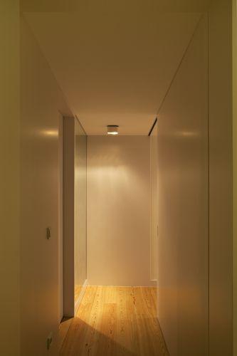 Foto do corredor de acesso aos dois quartos. Materiais, cores, iluminação e falta de ornamentos conferem ao espaço uma atmosfera moderna e requintada. Pelo conforto que proporciona, entretanto, a proposta não deixa de ser acolhedora