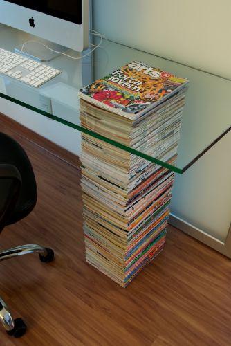 Revistas de arte da coleção do casal de proprietários foram usadas como pé da mesa de trabalho. Para dar firmeza à pilha, as revistas precisaram ser perfuradas (pela PontGraf) para a passagem de elemento estrutural (da ClipMetal) que efetivamente suporta o tampo da mesa