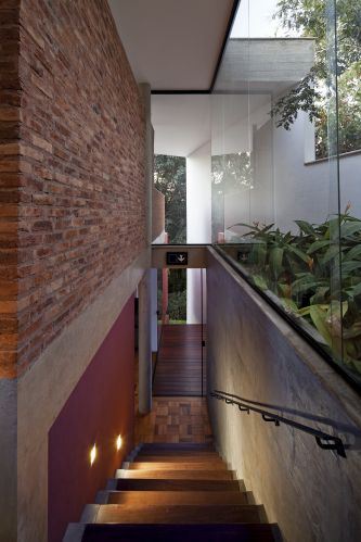 Escada de madeira, que leva ao pavimento dos dormitórios ( inferior), fica localizada na lateral da casa projetada por Bruno Santa Cecília, em Nova Lima (MG). Destaque para a estrutura de concreto e os tijolos aparentes (à esq.)