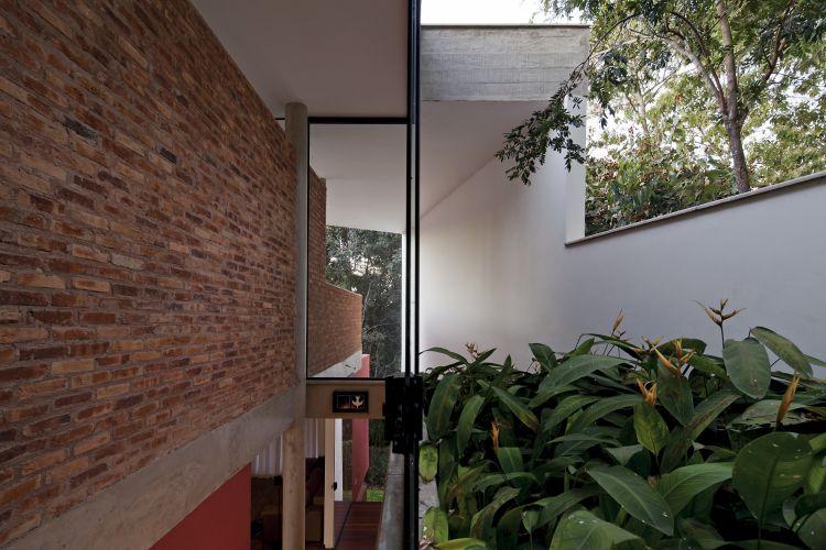 Fachada lateral da casa, onde fica a escada que leva ao pavimento inferior, dos dormitórios. A estrutura de concreto e os tijolos são aparentes na proposta arquitetônica de Bruno Santa Cecília