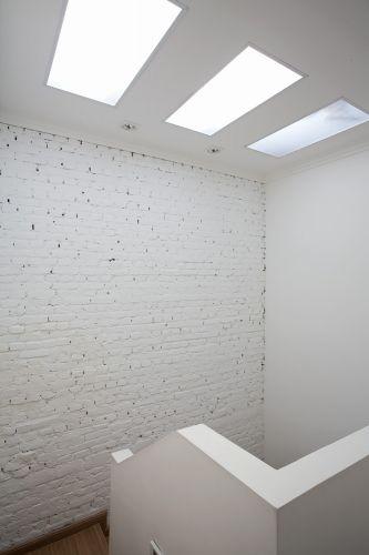 A escada recebe iluminação zenital a partir da abertura de uma claraboia com fechamento em policarbonato fosco e translúcido