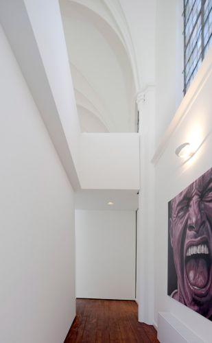 Na transformação da antiga igreja em Utrecht, na Holanda, em residência, o mezanino foi recortado e recebeu guarda-corpo de vidro. Todas as paredes foram pintadas de branco, inclusive o teto com seus arcos. Á direita, uma das obras de arte contemporâneas da nova residência, forte contraponto a antiga religiosidade do local. O trabalho de adaptação do templo em moradia é do escritório de arquitetura holandês Zecc Architecten