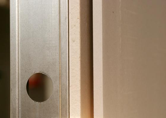 Montagem de parede de drywall mostra o perfil metálico com furo para passagem de dutos e as duas placas de gesso acartonado que compõem o sistema