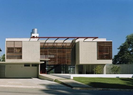 O concreto aparente é mais que uma opção de estilo: é estrutural. Na foto, painel de concreto aparente e brises de madeira compõem a fachada da casa projetada pelo arquiteto Mário Biselli