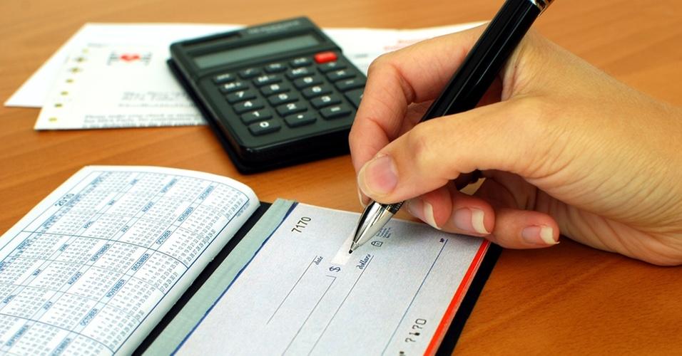 Imagem ilustrativa de mão assinando um cheque, com calculadora e contas ao fundo, simbolizando pagamento