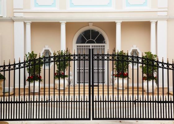 Fachada com portão de ferro de duas folhas. Dependendo das dimensões, o material pode tornar o portão pesado demais, dificultando a abertura manual ou exigindo um motor mais potente