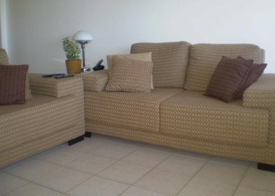 Marcel Steiner avalia que não cabem dois sofás na sala. Ele recomenda que o internauta substitua uma deles por uma poltrona, coloque um tapete e uma mesa de centro. Objetos<br> de decoração e quadros nas paredes, além de almofadas coloridas, completam a ambientação