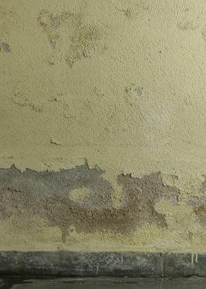 Pé de parede danificado por infiltração de água vinda do terreno e fundações. Entre os baldrames e as paredes da construção deve ser aplicado um isolamento