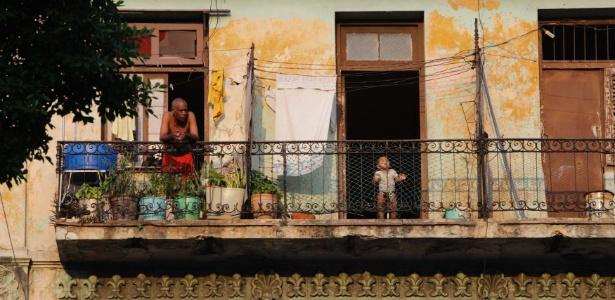 Homem e menino são fotografados em um balcão de uma casa na capital de Cuba, Havana - Reuters