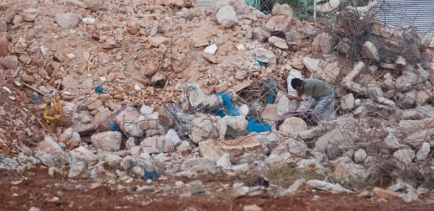 Homem retira ferragens de entulho decorrentes da demolição da antiga rodoviária que ficava na região da cracolândia