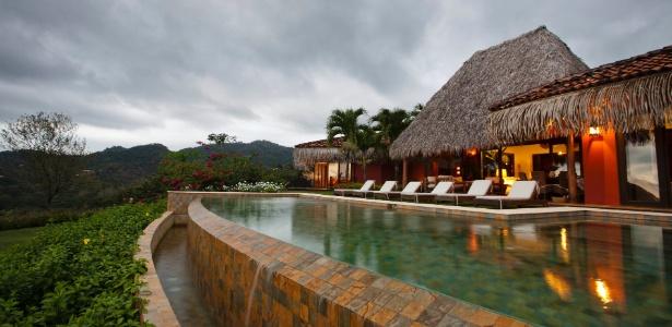 A piscina da casa da família Ewing na Costa Rica usa ladrilhos verdes como revestimento e está ao lado da sala de estar da residência, formando uma grande e agradável área de lazer - Tito Herrera/The New York Times