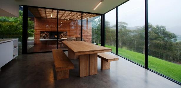 A sala de jantar da casa na Tasmânia tem vistas para o vale e para o Monte Wellington. Ao fundo, o pórtico de madeira, junto a lareira, transparece pelo plano de vidro do piso ao teto